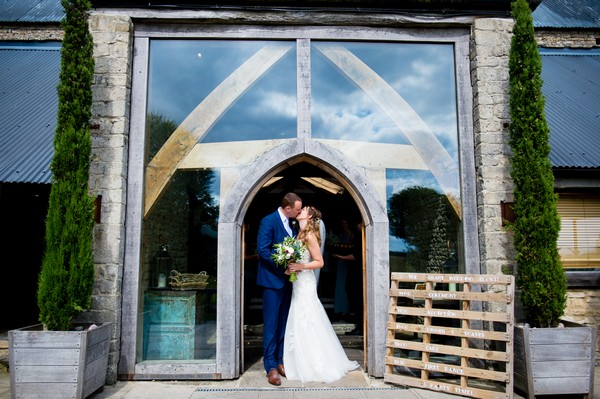 Bride and groom kissing at entrance of Cripps Barn