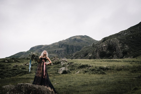 Bride wearing dark blue dress in countryside of Lake District
