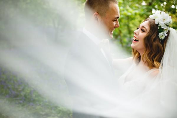 Bride and groom behind bride's veil