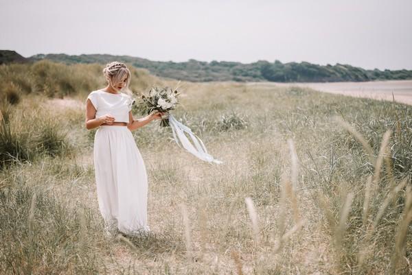 Bride walking on grass by beach