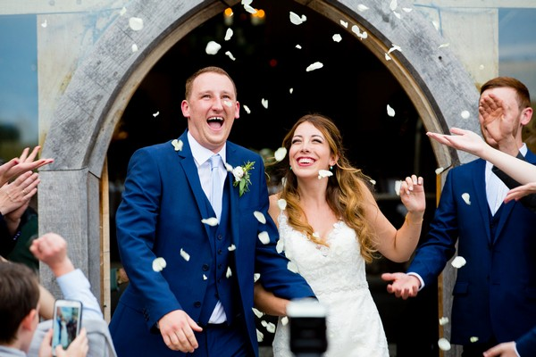 Bride and groom under confetti shower