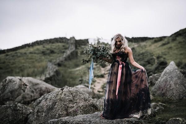 Bride wearing dark blue wedding dress walking over rocks in Lake District