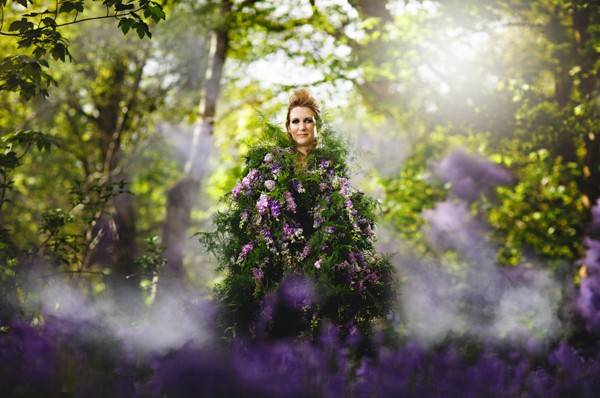 Bride in woodland covered in purple flowers and foliage