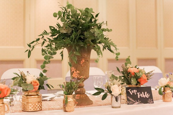 Urn of foliage with copper and gold votives of flowers on wedding table
