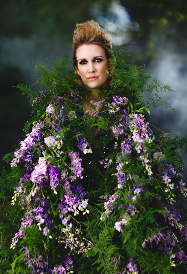 Bride wearing living cape of purple flowers and foliage