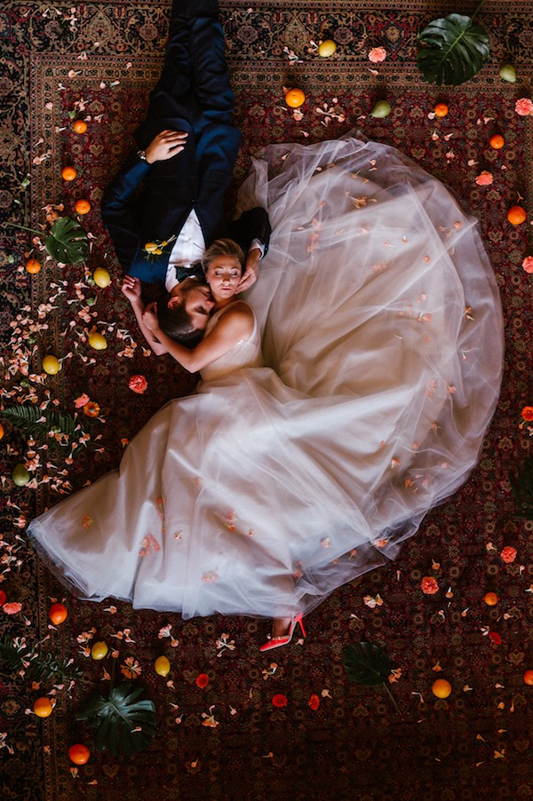 Bride and groom laying on floor surrounded by citrus fruit