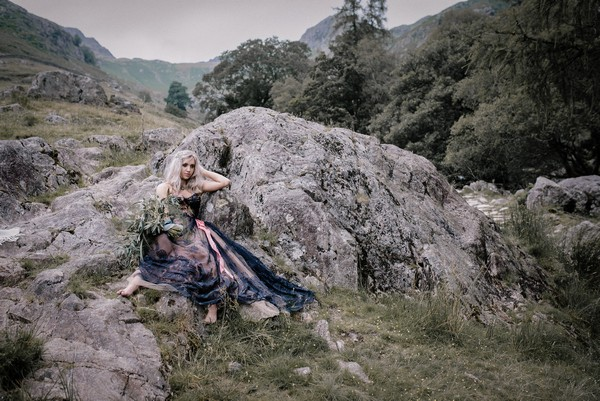 Bride sitting against rocks in Lake District