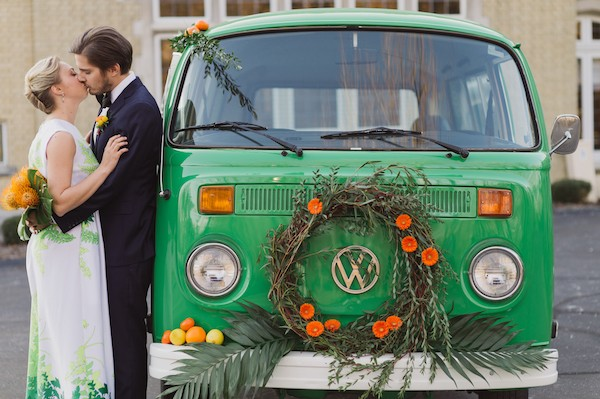 Bride and groom kissing by VW van with orange flower wreath and citrus fruits on the front