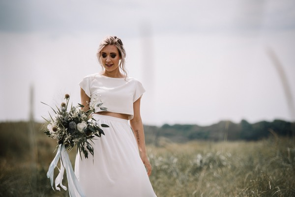 Bride wearing bridal separates holding bouquet