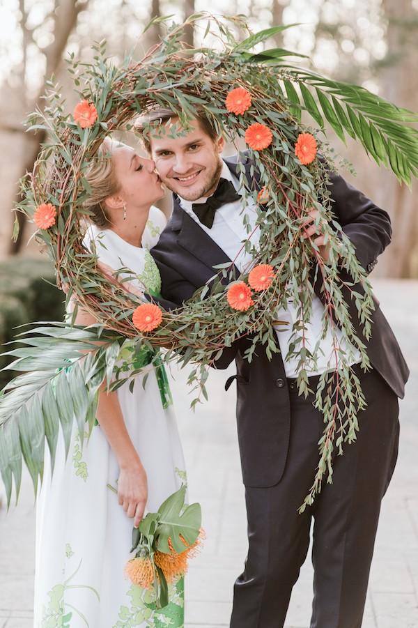 Bride kissing groom behind wreath of orange flowers