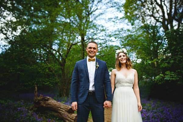 Bride and groom holding hands in woods