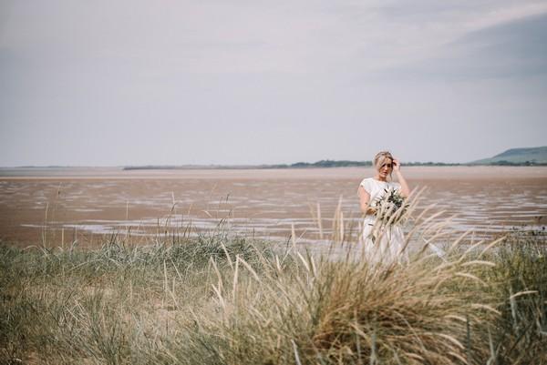 Bride by beach in Cumbria