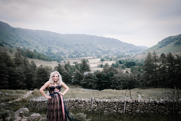 Bride with hands on hips in front of view of Lake District