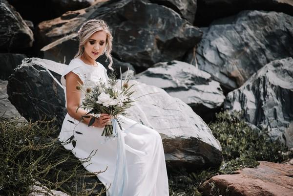 Bride sitting on rocks