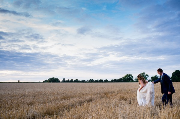 Bride and groom walking across wheat field