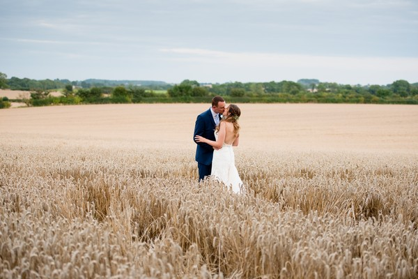 Bride and groom kissing in wheat field