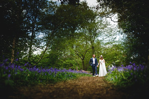 Bride and groom walking through woodland with bluebells