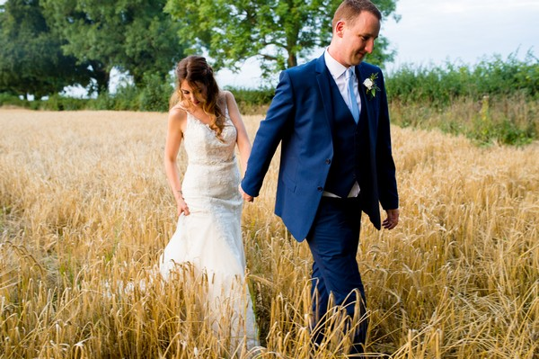 Bride and groom holding hands walking through wheat