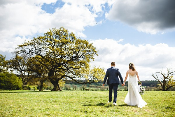 Bride and groom walking across field