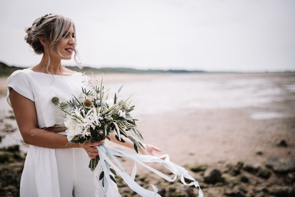 Bride holding bouquet on beach in Cumbria