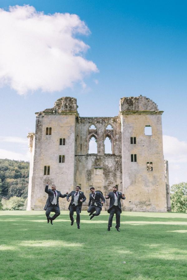 Groomsmen jumping in front of ruin