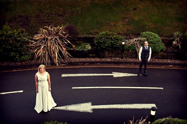 Bride and Groom in Road Next to Arrows