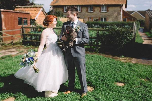 Bride with groom holding chicken
