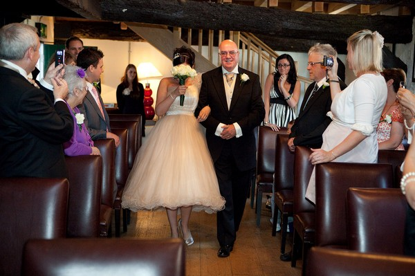Guests Taking Pictures As Bride Walks Down the Aisle Covering Face with Bouquet