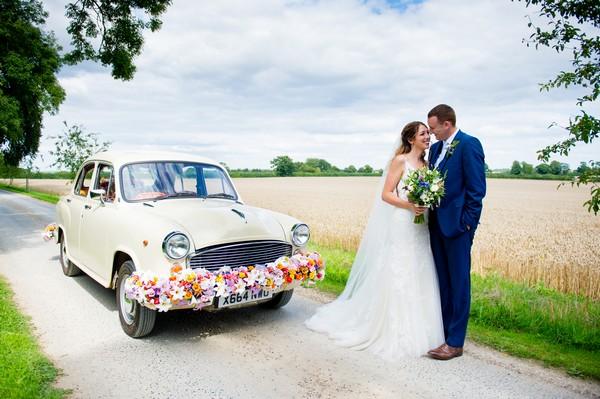 Bride and groom by Indian Ambassador car