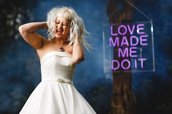 Rock n roll bride in front of neon sign which reads Love Made Me Do It