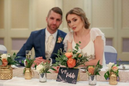 Bride and groom sitting at table with blush, copper and gold wedding styling