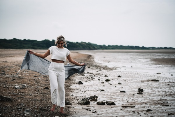 Bride holding out shawl on beach on Cumbrian Coastline in Lake District for Wild Spirit wedding shoot