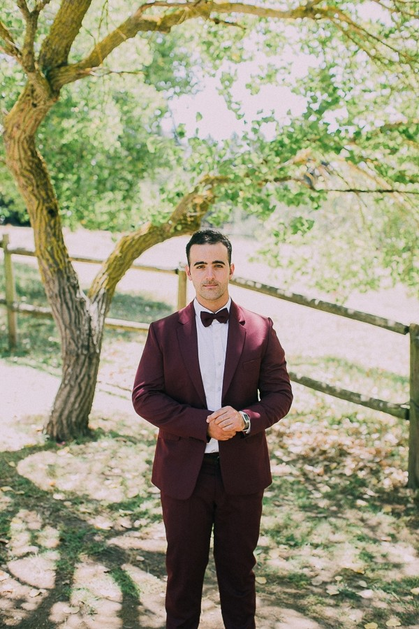 Groom wearing burgundy suit and bow tie