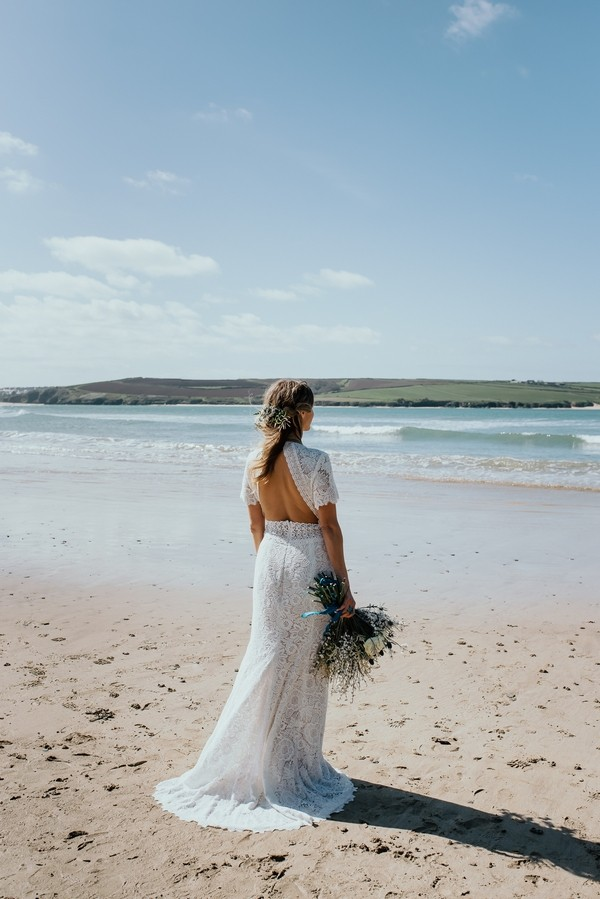 Bride with open back wedding dress looking at sea