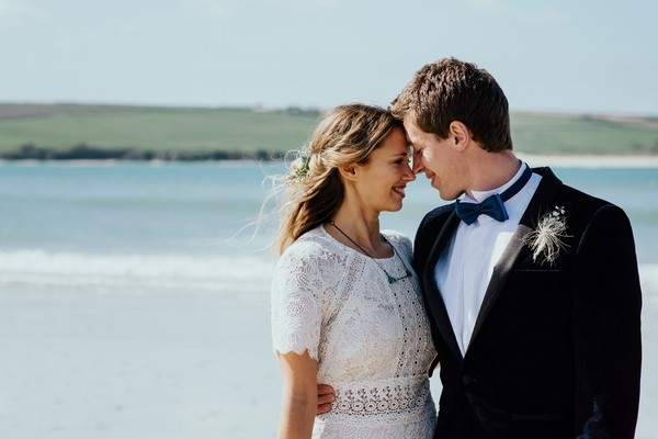Bride and groom touching heads on beach