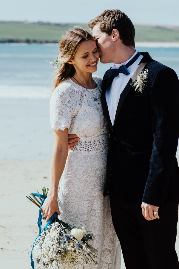 Groom kissing bride on cheek on beach