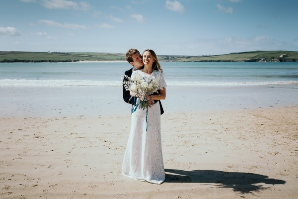 Groom behind bride with arms around her waist