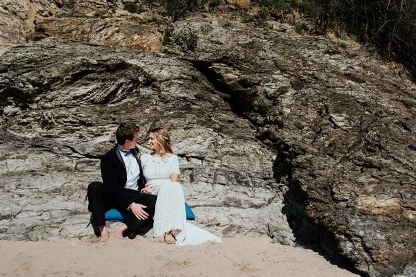 Bride and groom sitting by rocks on beach
