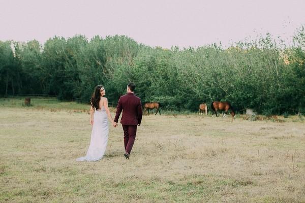 Bride and groom walking across field at Natte Valleij wedding