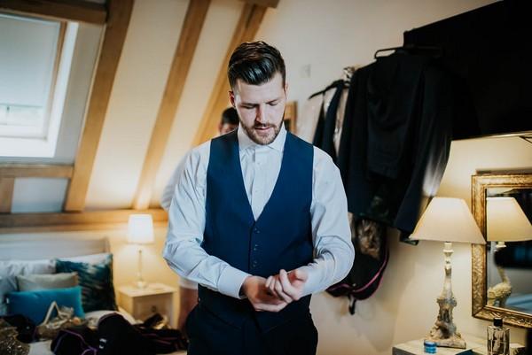 Groom getting dressed before wedding