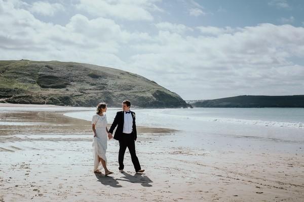 Bride and groom walking on beach