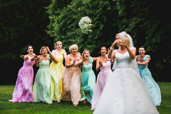 Bride throwing bouquet towards bridesmaids in colourful dresses - Picture by Aaron Storry Photography