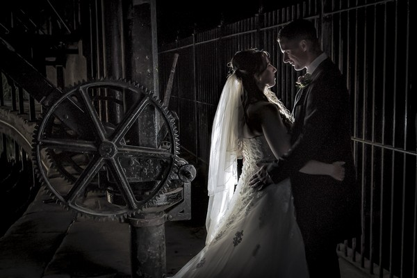 Bride and groom standing by large mechanical cog - Picture by Peter Anslow Photography