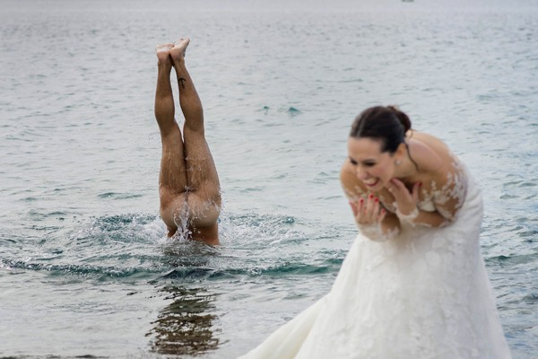 Bride laughing as naked man dives into water behind her - Picture by Photo-4U Pasquale Minniti