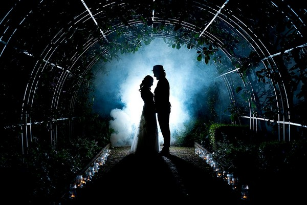 Silhouette of bride and groom in greenhouse surrounded by smoke - Picture by Matt Selby Photography