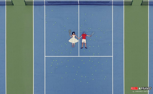 Aerial shot of bride and groom laying down on tennis court - Picture by Reels and Frames