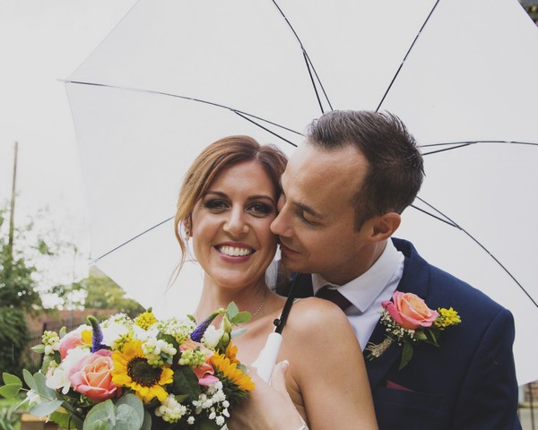 Smiling bride holding umbrella with groom about kiss her on cheek - Picture by Rebecca Gurden Photography