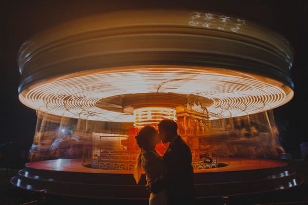 Bride and groom kissing in front of blurred fairgroung carousel - Picture by Rob Dodsworth Photography