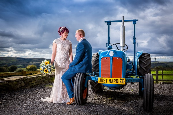Bride and groom next to tractor with Just Married number plate - Picture by SJPhotographers