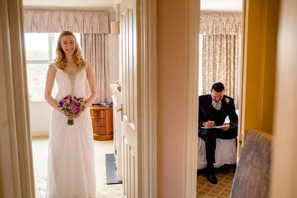 Bride stabding in one room as groom sits writing in the next - Picture by Stewart Girvan Photography